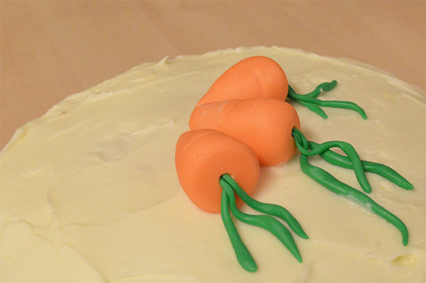 Decorating a carrot cake with cream cheese frosting